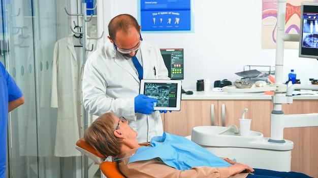 Orthodontist in handschoenen die een tablet vasthoudt en röntgenfoto's van de kaak aan de patiënt toont terwijl hij tijdens het consult een behandeling voorstelt. stomatologist presenteren aan oude vrouw tandheelkundige radiografie met behulp van moderne gadget.