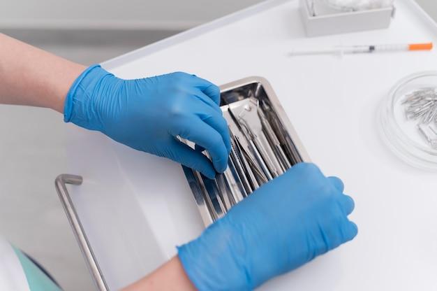 Orthodontist met latexhandschoenen die tandheelkundige apparatuur hanteert
