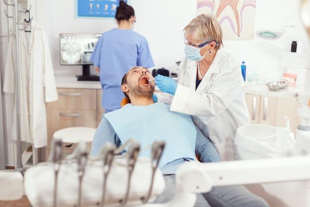 Orthodontist senior arts die kiespijnbehandeling doet bij zieke patiënt die operatiehulpmiddelen voorbereidt
