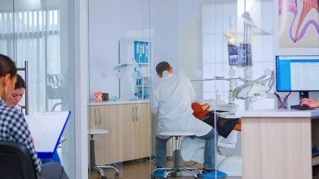 Orthodontist steekt de lamp aan tot hij een oudere vrouw onderzoekt terwijl patiënten wachten in de receptie en een tandheelkundig formulier invullen. tandarts in gesprek met vrouw met kiespijn zittend op stomatologische stoel.