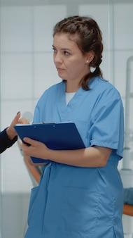 Orthodontisten werken team bespreken tandheelkundige operatie in de kliniek. tandarts en assistent staan in stomatologische kast terwijl ze praten over orale apparatuur en tandenonderzoek