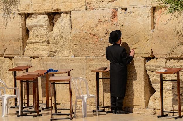 Orthodoxe joodse man die bij de westelijke muur in jeruzalem, israël bidt