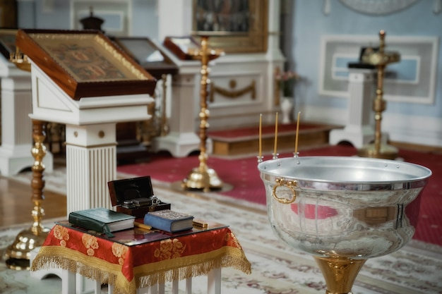 Orthodoxe kerk. kaarsen, kruis, icoon, gebedenboek, kaarsen en bijbel op tafel, doopvont. voorbereiding voor de doop van pasgeboren kind in wijwater. sacrament van de doop