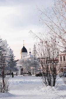 Orthodoxe kerk. winterlandschap. winterweg en bomen bedekt met sneeuw.