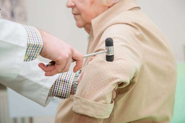 Orthopedisch chirurg die de kniereflex onderzoekt. de arts controleert de fysiologische reflex, de testhamer.