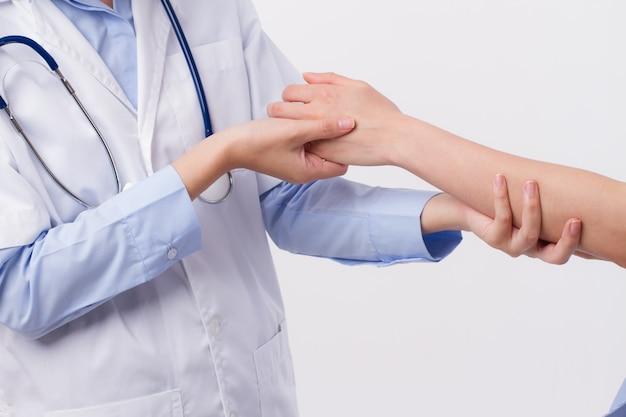 Orthopedische arts die arm van de patiënt inspecteert