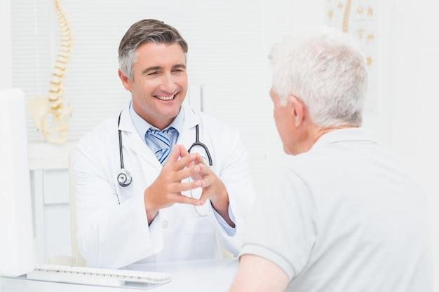 Orthopedische arts die met hogere patiënt bespreekt