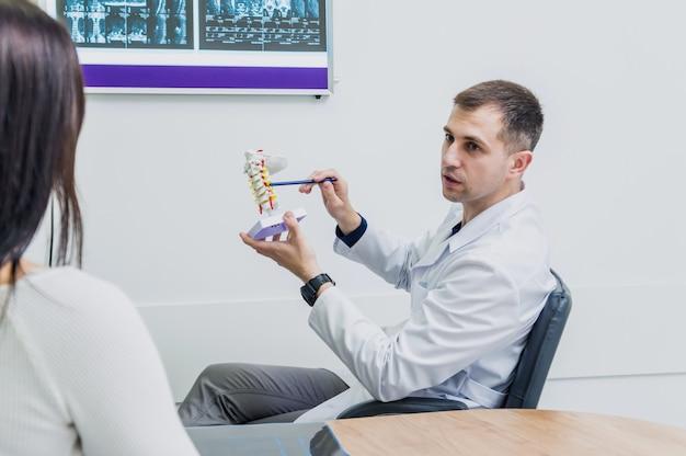 Orthopedist die wervelkolommodel tonen aan patiënt in het ziekenhuis