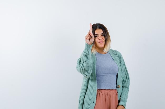 Ortrait die van vrouw greep op een minuutgebaar in vrijetijdskleding toont en zelfverzekerd vooraanzicht kijkt