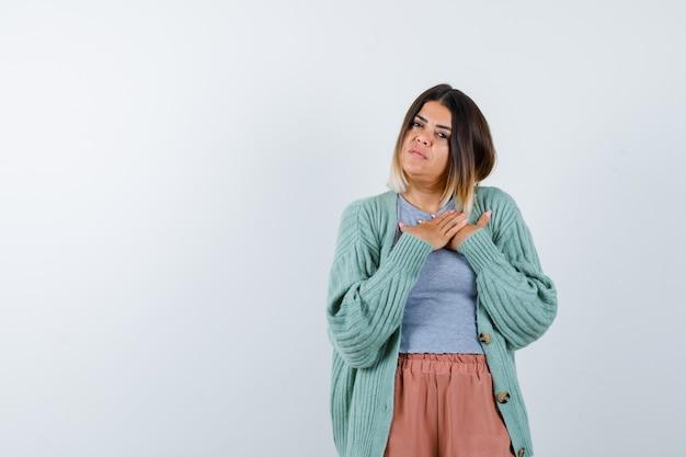 Ortrait die van vrouw handen op borst in vrijetijdskleding houdt en peinzend vooraanzicht kijkt