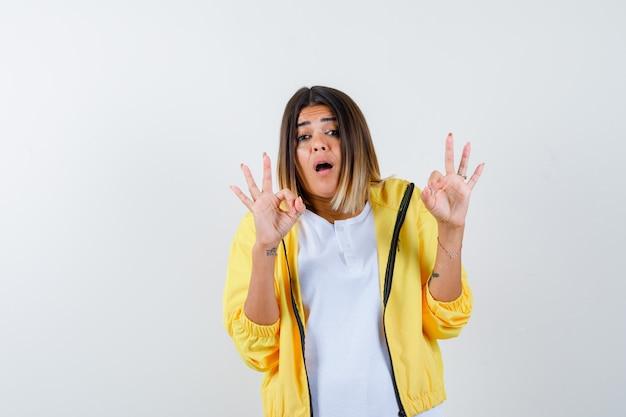 Ortrait die van wijfje ok gebaar in t-shirt, jasje toont en verbaasd vooraanzicht kijkt