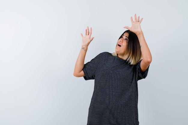 Ortrait van dame die handen opheft om zich in zwart t-shirt te verdedigen en bang vooraanzicht kijkt