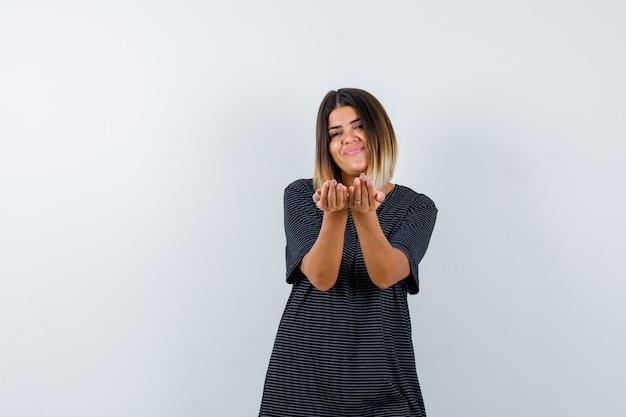 Ortrait van dame die het ontvangen of geven gebaar in zwart t-shirt maakt en heel vooraanzicht kijkt