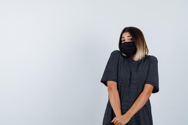 Ortrait van dame hand in hand voor haar in zwarte jurk, medisch masker en op zoek beschaamd vooraanzicht