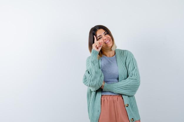 Ortrait van de vrouw die zich in het denken bevindt stelt in vrijetijdskleding en kijkt gelukkig vooraanzicht