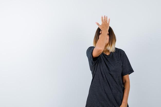 Ortrait van jong wijfje dat hand op voorhoofd in polokleding houdt en vergeetachtig vooraanzicht kijkt