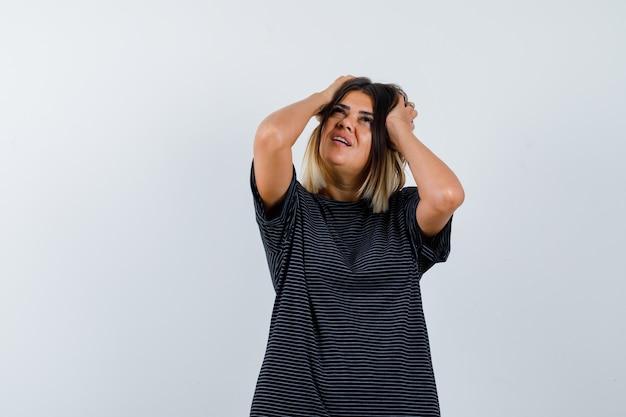 Ortrait van jonge dame hand in hand op het hoofd tijdens het kijken in polokleding en op zoek doordachte vooraanzicht