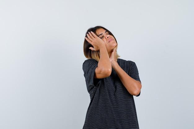 Ortrait van jonge dame hand in hand op hoofd en kin in polokleding en op zoek vermoeid vooraanzicht