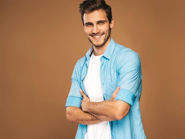Ortrait van knappe lachende stijlvolle jongeman model gekleed in blauw shirt kleding. mode man die zich voordeed. gekruiste armen
