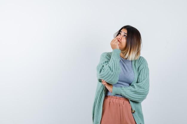 Ortrait van vrouw die hand op kin in vrijetijdskleding houdt en peinzend vooraanzicht kijkt