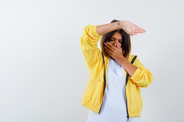 Ortrait van vrouw die hand op mond houdt, stopgebaar in t-shirt, jasje toont en verontrust vooraanzicht kijkt