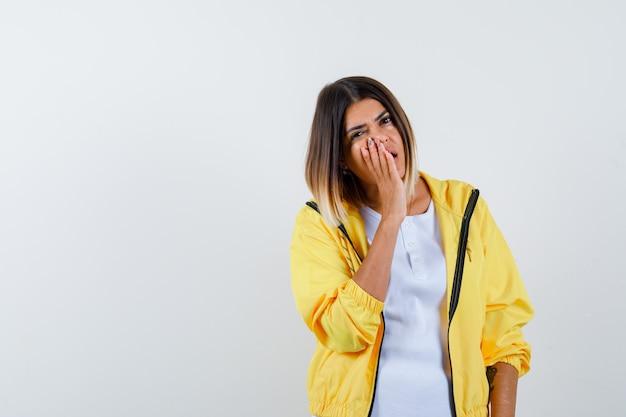 Ortrait van vrouwelijke hand houden in de buurt van open mond in t-shirt, jasje en op zoek verbaasd vooraanzicht