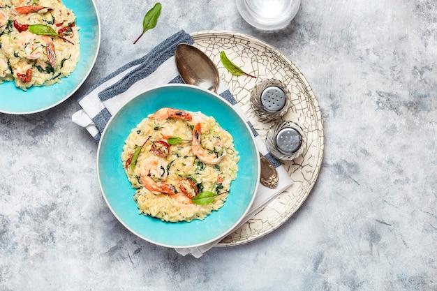 Orzo pasta ala risotto met gamba's, zongedroogde tomaten en spinazie