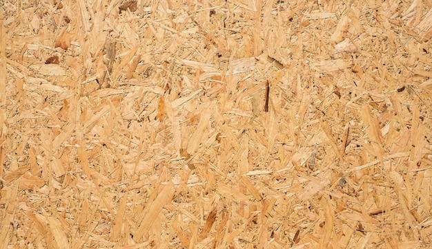 Osb-plaat is gemaakt van bruine houtsnippers die samengeperst zijn tot een houten vloer.
