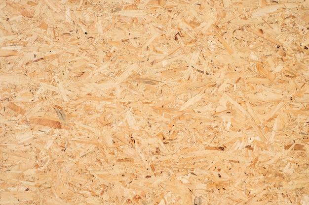 Osb-plaat is gemaakt van bruine houtsnippers die tegen elkaar zijn geperst tot een houten vloer.