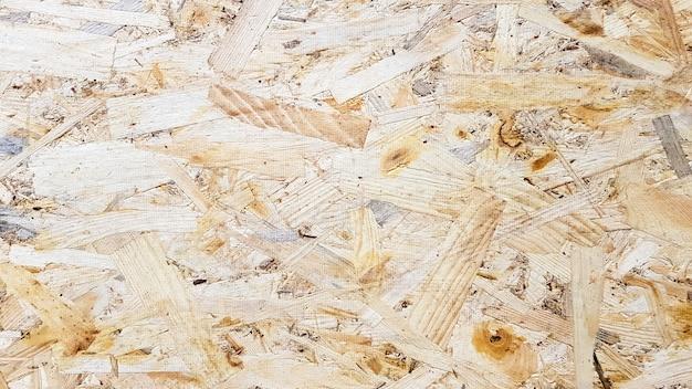Osb plaat is gemaakt van geperst bruin houtkrullen. zolder muur oppervlakken. materiaal voor het bouwen van een huis.