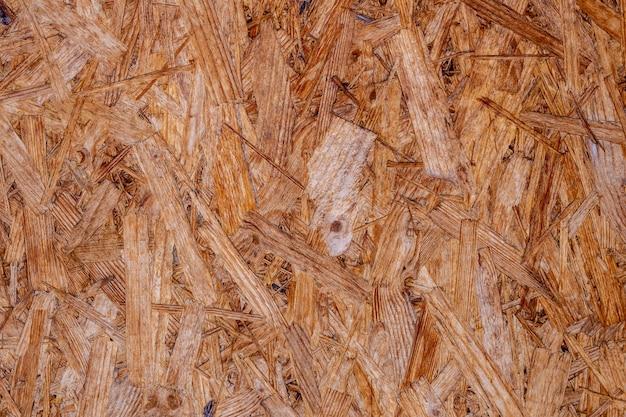 Osb-platen zijn gemaakt van bruine houtsnippers die in een houten achtergrond zijn geschuurd.