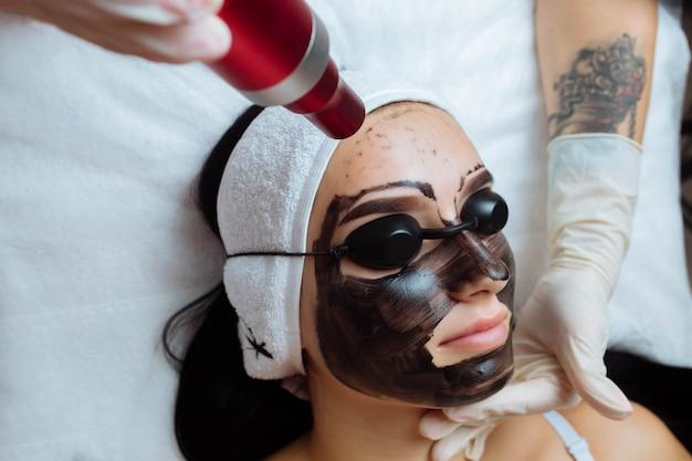 Osmetologen maken met de hand hardware carbon peeling door jonge mooie klantvrouw in veiligheid
