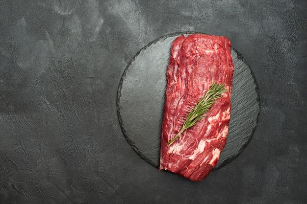 Ossenhaas biefstuk. rauwe biefstuk met rozemarijn op zwart