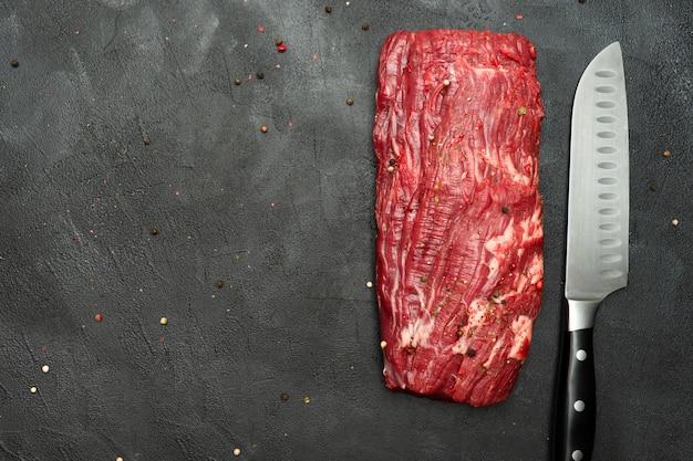 Ossenhaas biefstuk. raw beef steak met mes op zwart