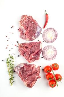 Ossenhaas. filet mignon. grote stukken vlees met verse groenten, tomaten, kruiden en specerijen op een witte plaat. bovenaanzicht.
