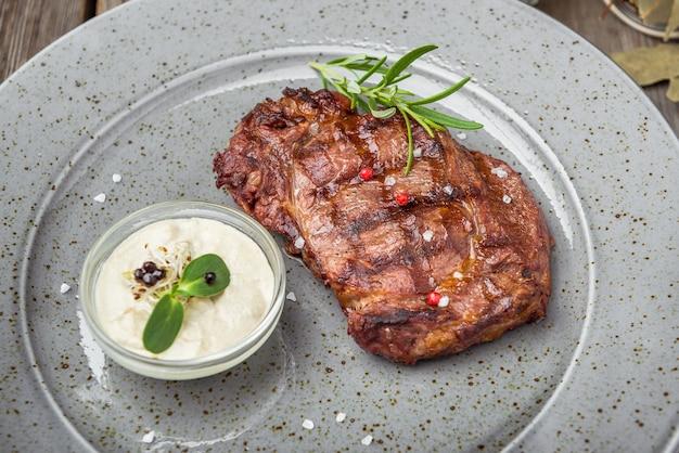 Ossenhaas steak op plaat met saus, op een houten tafel