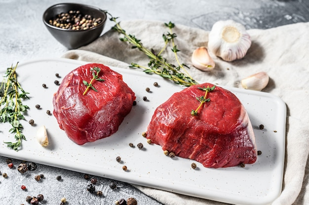 Ossenhaas van marmer. het ruwe lapje vlees van filethaakwerkmignon op een wit hakbord.