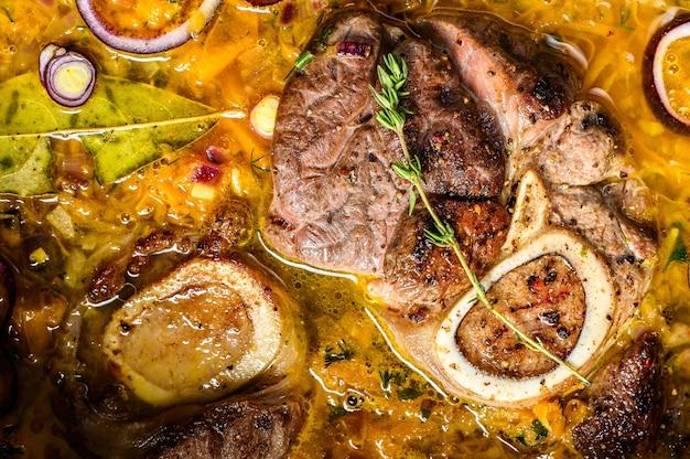 Ossobuco vleesstoofpotje met groenten. osso buco. grijze achtergrond.