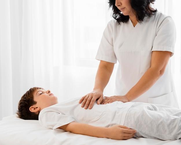Osteopaat die een kind behandelt door zijn buik te masseren