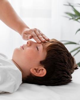 Osteopaat die een kind behandelt door zijn hoofd te masseren