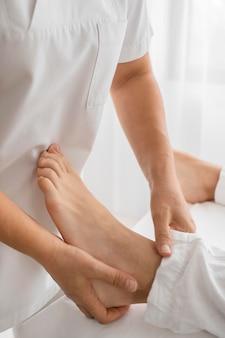 Osteopaat die een patiënt op zijn voeten behandelt