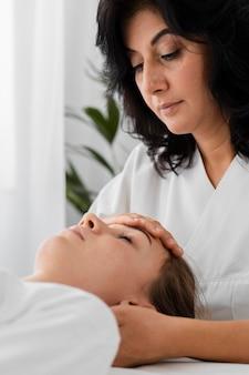 Osteopaat die een vrouwelijke patiënt behandelt door haar gezicht te masseren