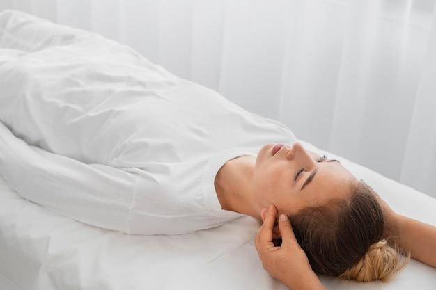 Osteopaat die een vrouwelijke patiënt binnenshuis behandelt