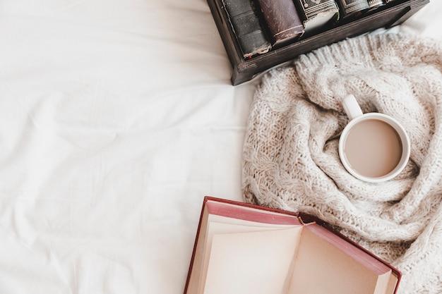 Otebook en doos met boeken in de buurt van warme drank in plaid