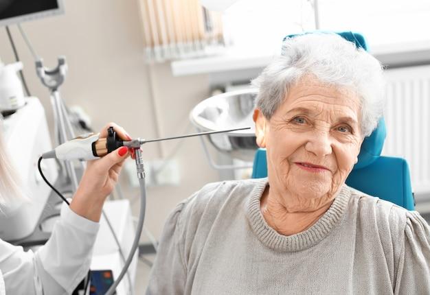Otolaryngologist die het oor van de hogere vrouw met ent-telescoop in het ziekenhuis onderzoekt. gehoorprobleem