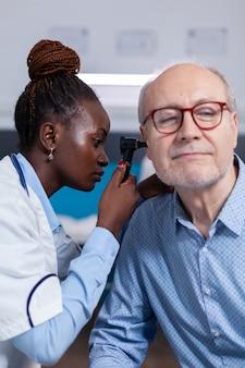 Otoloog van afrikaanse etniciteit die oudere patiënt raadpleegt