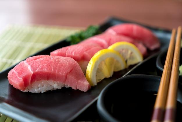 Otoro-tonijnsushi op zwarte plaat samen met japanse saus en groene bladdecoratie.