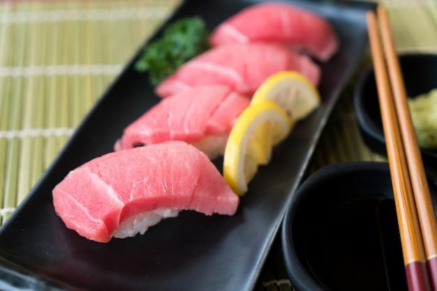 Otoro-tonijnsushi op zwarte plaat samen met japanse saus en groene bladdecoratie,