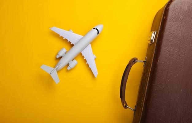 Oud bagage en vliegtuigbeeldje op gele oppervlakte