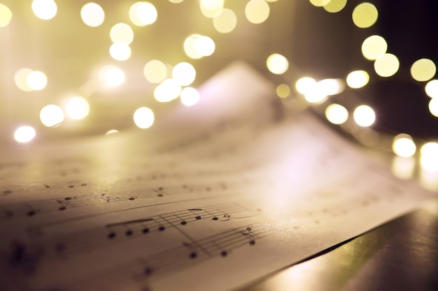 Oud blad met noten van de kerstmismuziek als achtergrond tegen vage lichten. kerst muziek concept